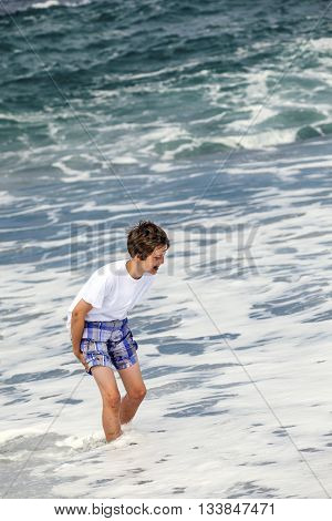 Boy Has Fun In The Spume At The Black Volcanic Beach