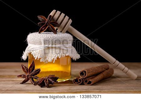 jar of honey, dipper, star anise and cinnamon on wood on black background