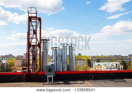 shopping center ventilation system. ventilation pipe on the background of summer city and blue sky with clouds. copy space for your text