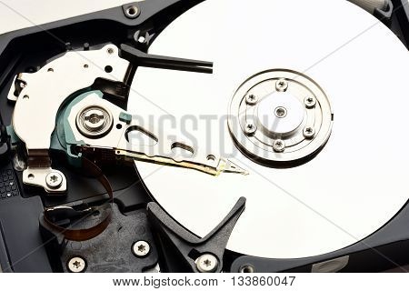 Computer hard disk drive internals with exposed disc surface and heads close up