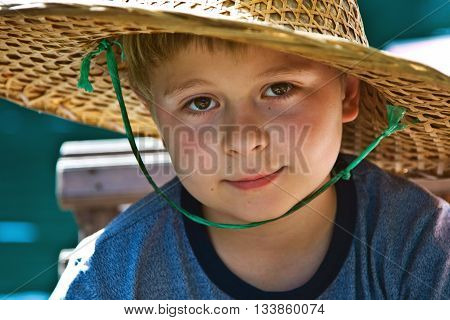 Child Is Wearing A Hat Made Of Bamboo During A Boattrip