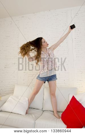 young attractive girl playing standing on top of on home sofa couch taking selfie portrait with mobile phone having fun laughing smiling happy and playful and making funny faces