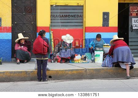 Cajamarca Peru - June 10 2016: Andean women sit on sidewalk and sell fruit in Cajamarca Peru on June 10 2016