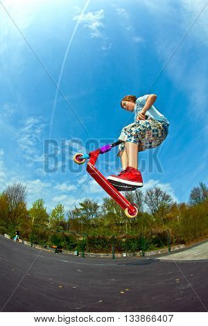 Boy Is Jumping With A Scooter Over A Spine In The Skate Parc