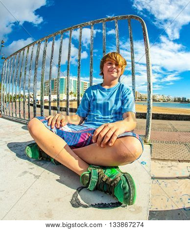 Cute Boy Sitting At The Skate Park