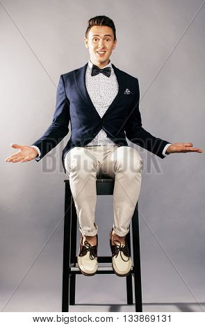 young handsoman businessman fooling aroung with chair, woundering gesturing, lifestyle people concept, wearing bowtie