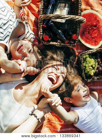 cute happy family on picnic laying on green grass mother and kids, warm summer vacations close up, brother and sister, lifestyle people concept