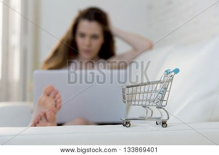 little toy replica of shopping trolley and young woman with laptop computer using internet for online shopping lying at home sofa couch relaxed in e-commerce and business concept