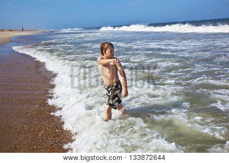 Cute Boy Has Fun In The Stormy Beach