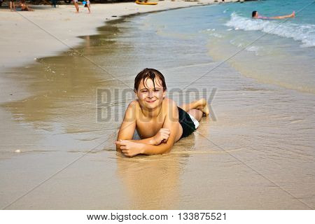 Young Boy Is Lying At The Beach And Enjoying The Warmness Of The Water