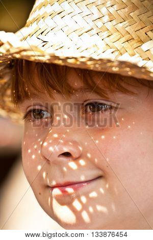 Young Boy With Straw Hat Is Happy And Smiles