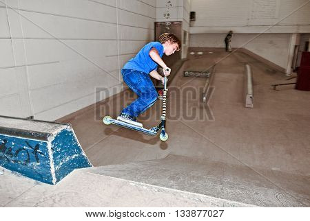Boy With Scooter Is Going Airborne In The Skate Hall