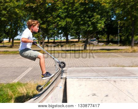 Boy Has Fun At The Skate Park With His Scooter