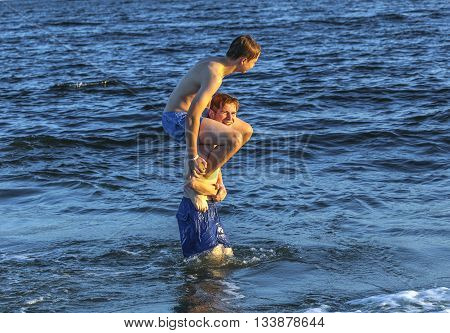 Boys Have Fun Playing Piggyback In The Ocean
