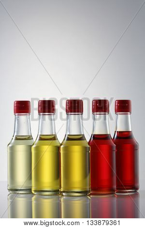 palm oil, sesame seed oil, olive oil, grape seed oil and corn oil in  glass bottle over white background