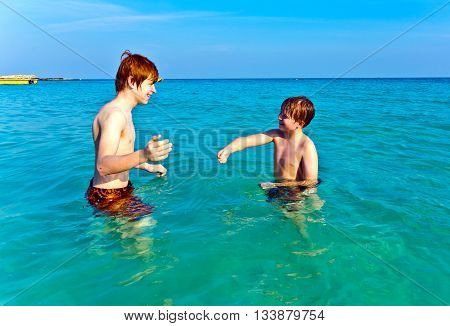 Brothers  Enjoying The Clear Warm Water At The Beautiful Beach