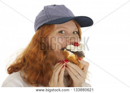 Female baker chef with red hair eating pastry isolated over white background