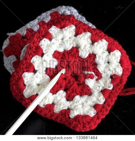 Red and white homemade crocheted woollen square.