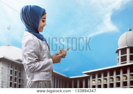 Muslim Woman Typing On Cellphone