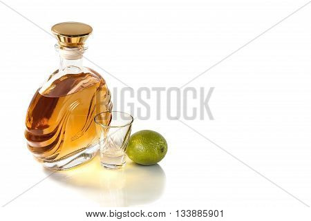 Bottle and a shot glass of tequila with lime on a white background