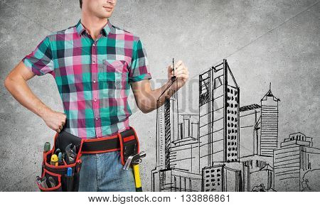 Young man builder with ruler in hands draw construction model
