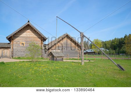 PSKOV REGION, RUSSIA - MAY 08, 2016: Ancient well on wooden farmhouses. Reconstruction of a farm of the XVIII century in the village Bugrovo. Tourist landmark of the Pushkin Hills