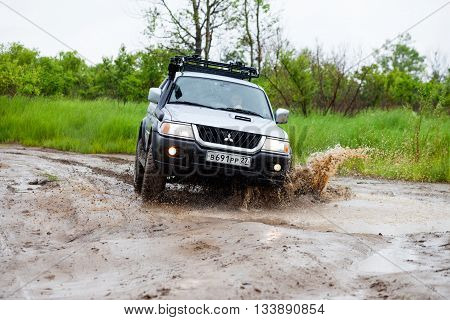 NIKOLAEVKA RUSSIA - JUNE 11 2016: Mitsubishi Pajero moving by water in the rain making lots of splashes