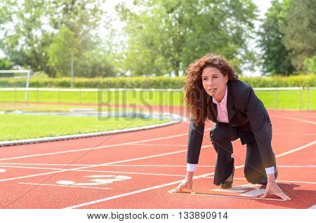 Determined businesswoman in the starting position crouching down on a race track in a sports stadium as she prepares to meet a challenge and beat the competition