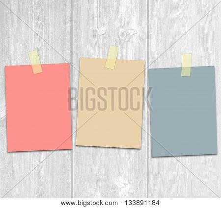 Three colored adhesive paper on a white wooden background.