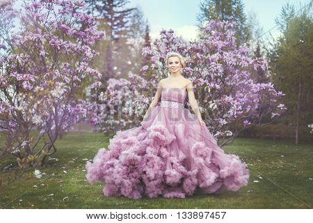 Blonde woman among flowering trees she wore a luxuriant dress.