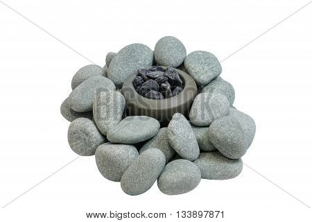 Pile of smooth stones around the stone bowl with stones. Objects on a white background.