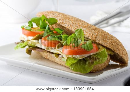 Healthy sandwich with omelet fresh cheese tomato and watercress