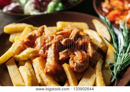French fries with meat close-up. Portion of French fries with pork.