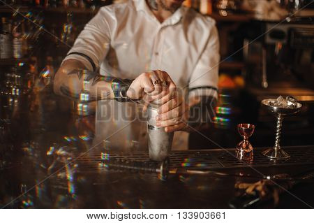 Close up photo of a bartender standing at the counter holding a shaker no face