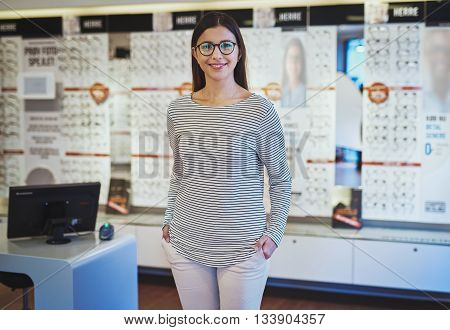 Cute young woman wearing prescription eyeglasses and striped shirt with hands in pockets next to register and display in store
