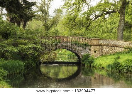 Stunning Landscape Image Of Old Medieval Bridge Over River With Mirror Like Reflections Of Countrysi