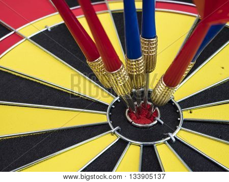Dart arrows pin in the center of dart board (Business Concept)