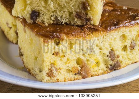 Sweet fruit cake with raisins in blue plate on wooden table