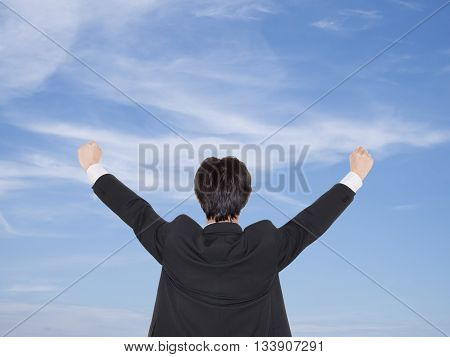 Single smart business man wear black suit joyful / happiness show hand up on the blue sky.