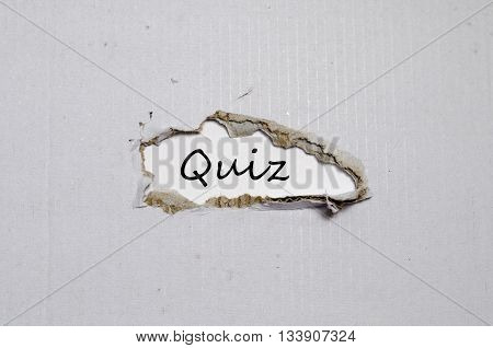 The word quiz appearing behind torn paper.
