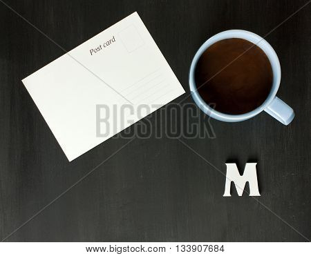 A postcard a cup of hot chocolate and the letter 'M' on a dark wooden boards texture with a place for text; traveling concept