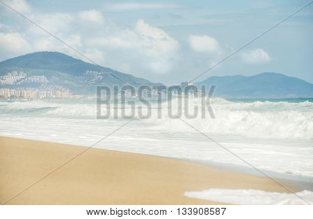 Waves in the sea with mountains and town at the back. Beach of Alanya, Mediterranean coast of Turkey
