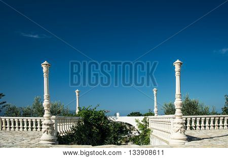 Antique balustrade with entrance to the garden and clear blue sky background. white stone empty terrace. mediterranean architecture
