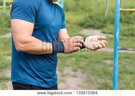 Strong young athlete. Strong young athlete is engaged in on an abandoned sports field. Athlete Outdoors. Toned image.
