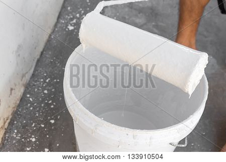 White paint dripping with paint roller, on the edge paint bucket.(select focus front  paint roller and Blur blurred background)