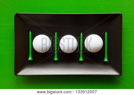 Black ceramic dishes with golf balls and wooden tees on over green background rectangle dish