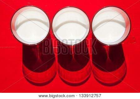 Three glasses of milk on the red wooden table - Flat Lay Photography