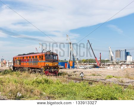 Old diesel electric locomotive is passing the construction site near the urban station.