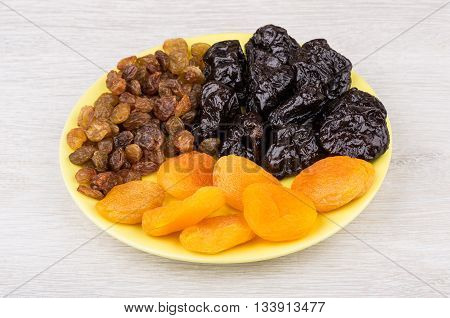 Prunes, Driet Apricots And Raisins In Saucer On Table