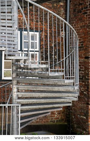 modern exterior spiral staircase of metal in the backyard on an old brick building fire escape in the old town
